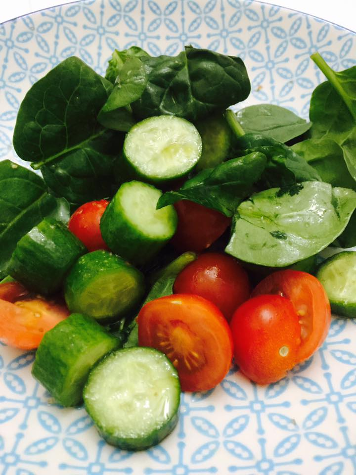 Spinach tomato and cucumber salad with olive oil and smoked salt.